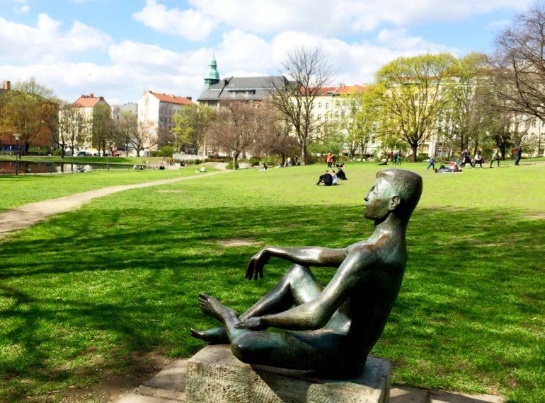 A imagem mostra uma escultura de uma pessoa sentada, meditando, no meio de um gramado de uma praça.