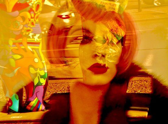A imagem mostra uma manequim ruiva exposta numa vitrine. Reflexos coloridos compõem a cena.