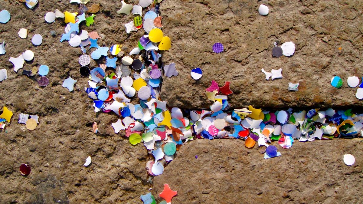 #paracegover A imagem mostra restos de confete no vão de uma calçada.