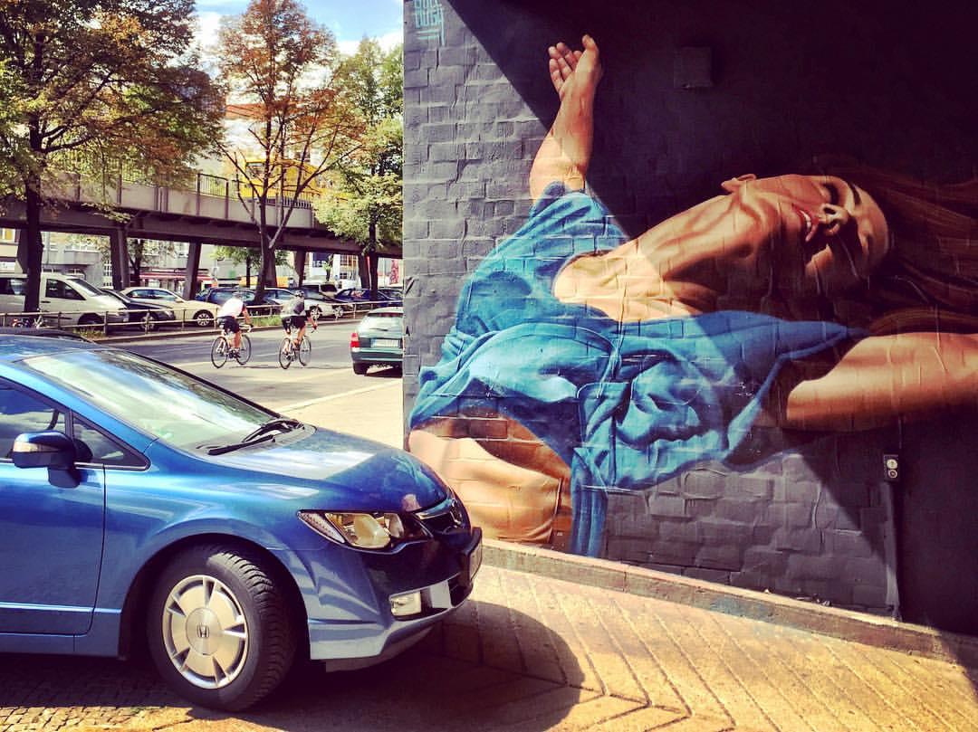 """9. Quando a vida real e a streetart resolvem conversar, o resultado é sempre surpreendente. Você consegue imaginar uma maneira mais glamourosa de dizer """"pode me atropelar""""?...rsrsrs #paracegover A imagem mostra a entrada de uma garagem com um grafite hiperrealista de uma mulher com uma camiseta azul. Um carro também azul está esperando o portão ser aberto. Na rua é possível ver os trilhos do metrô (suspensos) e dois ciclistas ( Bülowstraße)."""