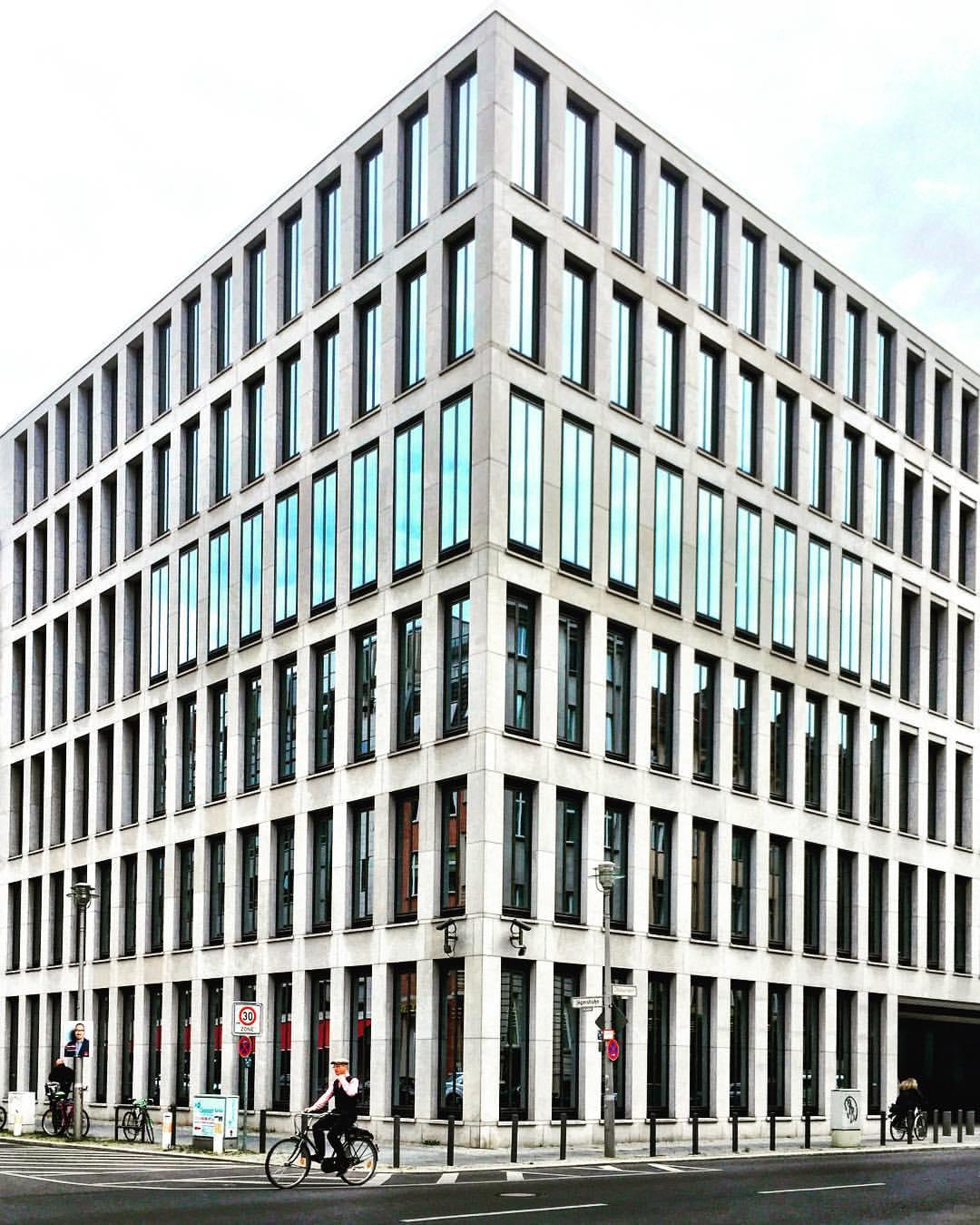 7. Adoro paisagens simétricas! E você? #paracegover A imagem mostra um prédio de concreto e vidro visto de esquina, em perfeita simetria. No canto esquerdo, passa um ciclista ( Französische Straße).