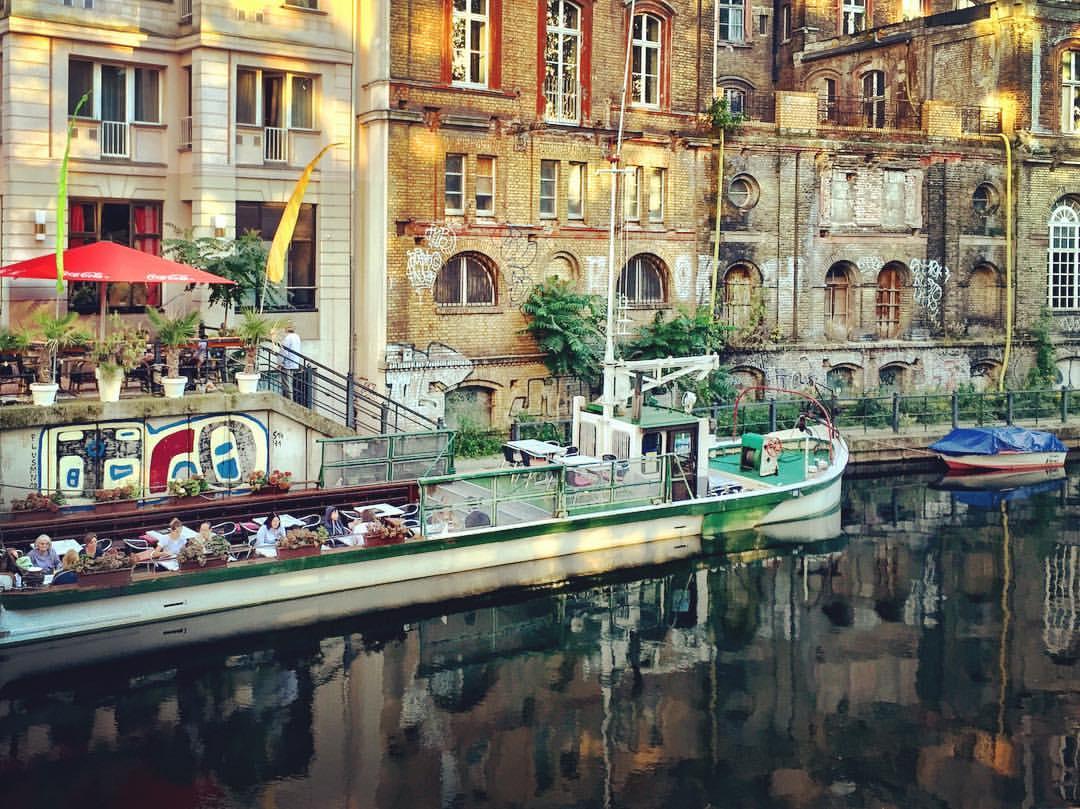 6. Essa luz no final de tarde me embriaga... #paracegover A imagem mostra um barco restaurante visto de lado, de cima de uma ponte. Há pessoas nele saboreando comida indiana. Ao fundo, paredes de construções antigas, douradas pela luz do sol. Parte da cena se reflete na água do canal do rio Spree.