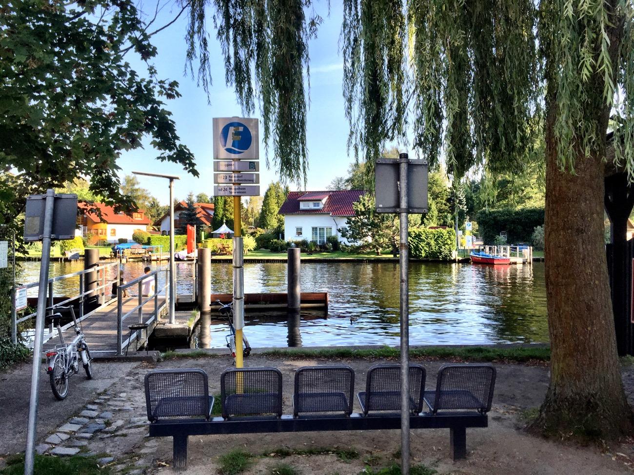 #paracegover A imagem mostra o ponto onde se espera pelo barco, com bancos de ferro em frente a um píer. Você já viu um ponto de transporte público mais charmoso?
