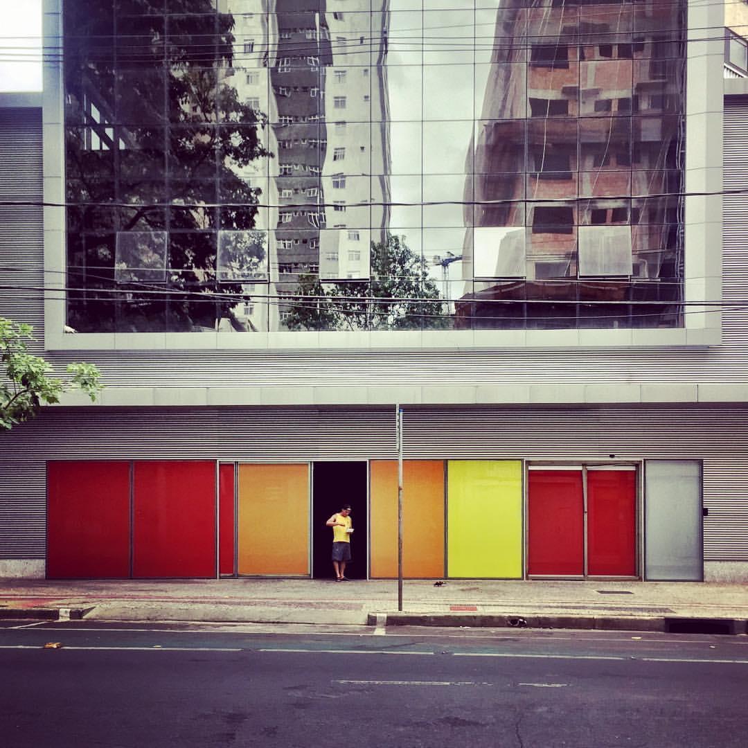 A imagem mostra a fachada de um prédio com superfícies nas cores vermelho, laranja e amarelo. Uma pessoa de camiseta amarela está na porta. A parte superior é de vidro espelhado. — at Circus Rock Bar.