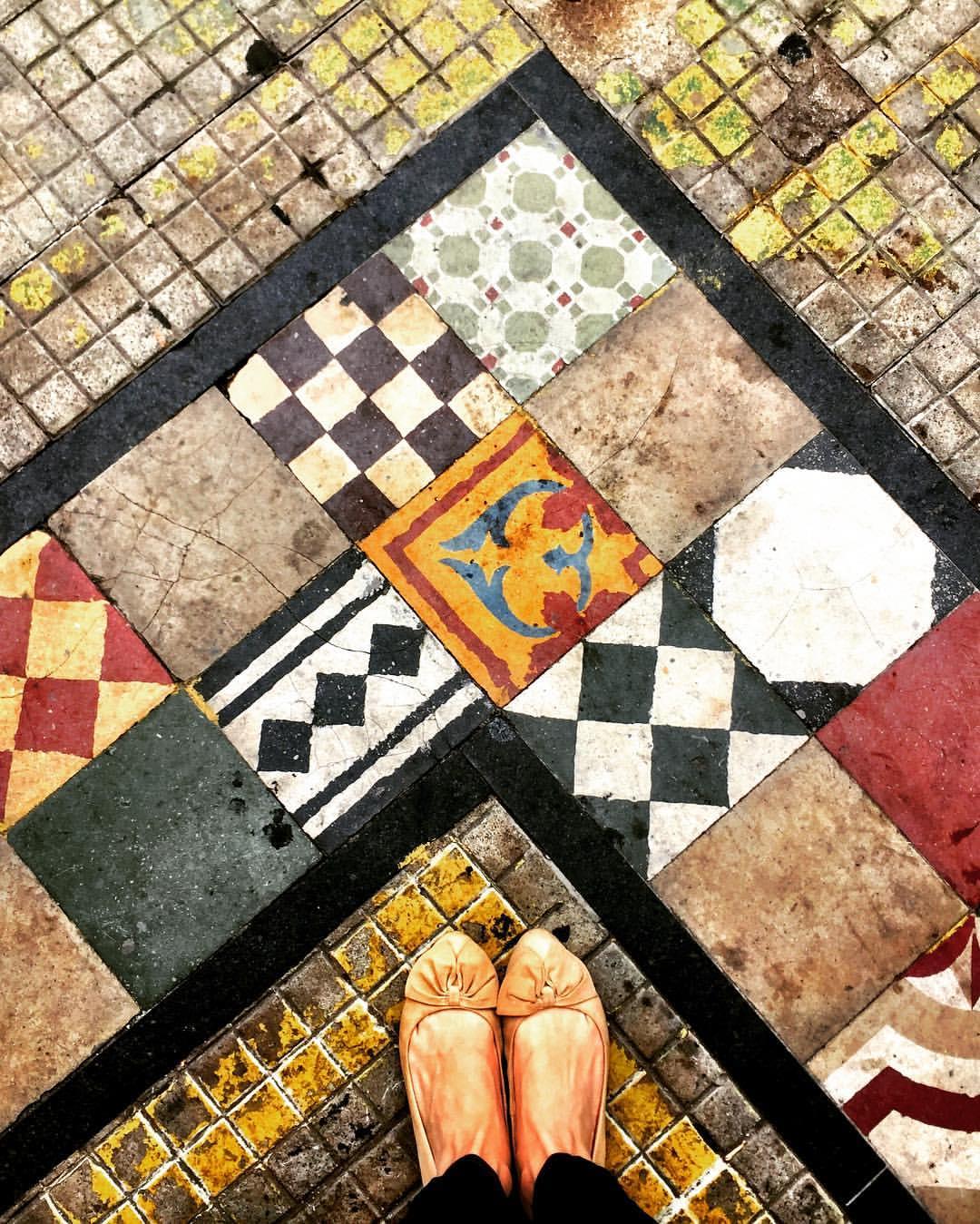 #paracegover A imagem mostra uma calçada decorada com azulejos hidráulicos coloridos, formando um ângulo reto. Meus pés aparecem no canto inferior, na base do triângulo. — at Boi lourdes.