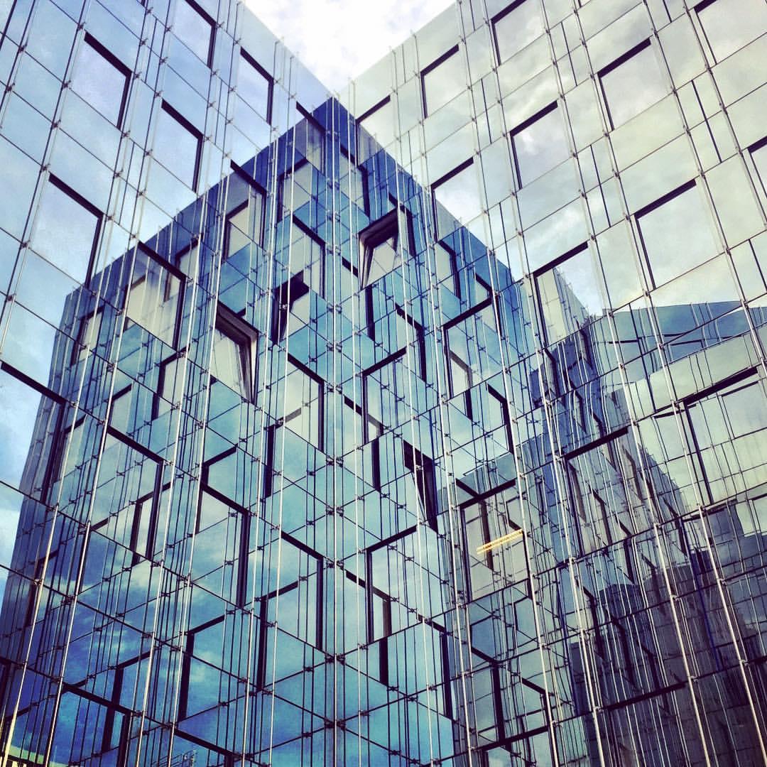 #paracegover A imagem mostra dois prédios cobertos de vidro espelhado, em que um reflete o outro. — at Kaiserin-Augusta-Allee.