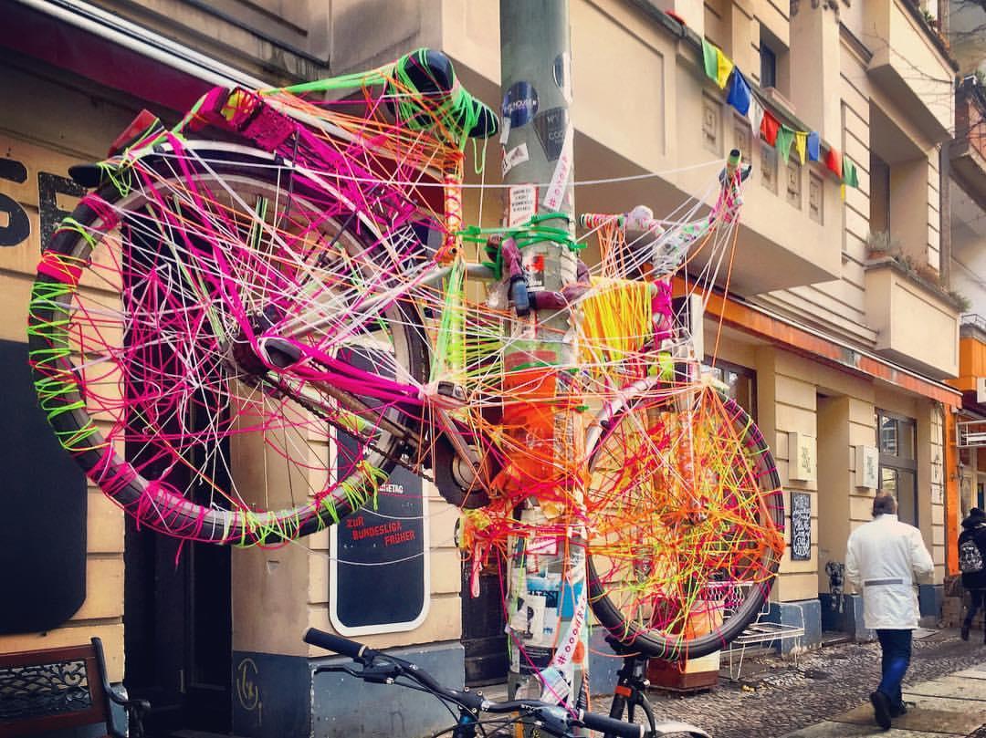 #paracegover A imagem mostra uma bicicleta pendurada num poste, toda coberta por linhas de cores diversas, fazendo as vezes de uma escultura, totalmente integrada ao ambiente. Uma das sacadas do prédio que aparece ao fundo é enfeitada com bandeirinhas coloridas. O povo desse bairro (Friedrischshain) gosta de cenários coloridos (eu também). — at Gabriel-Max-Straße.
