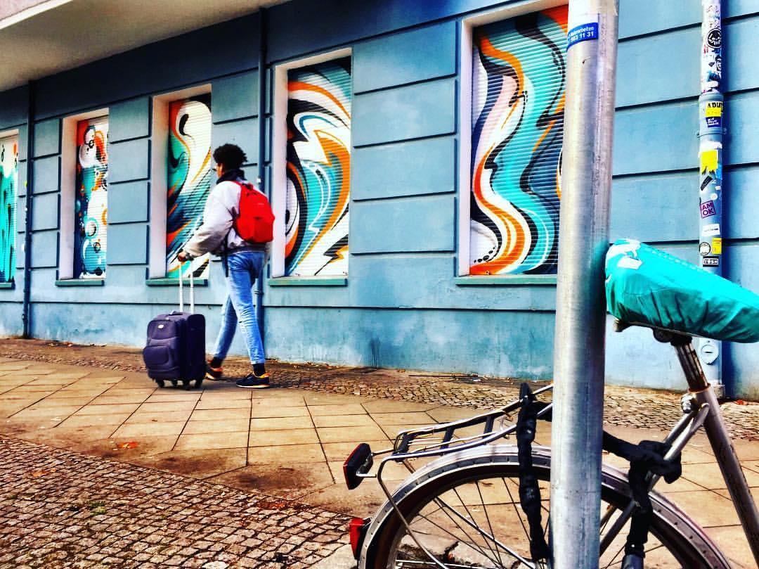 #paracegover A imagem mostra um homem andando por uma calçada; ele carrega uma mochila vermelha. A parede do prédio é azul e as venezianas das janelas estão pintadas com figuras abstratas em tons de turquesa, exatamente da cor do banco da bicicleta estacionada que aparece no canto inferior direito da foto. — at Kopernikusstraße.