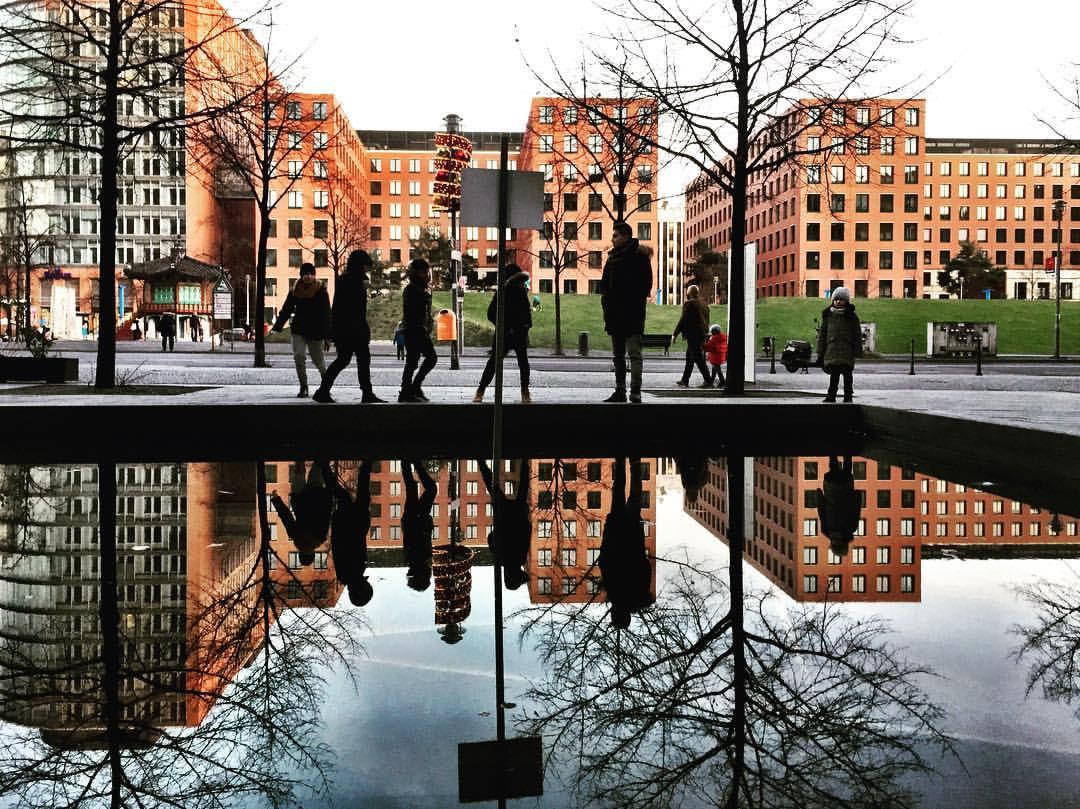 #paracegover A imagem mostra um grupo de pessoas à beira de um espelho d' água. Os prédios que aparecem ao fundo, assim como as árvores sem folhas são refletidas também. — at Potsdamer Platz.