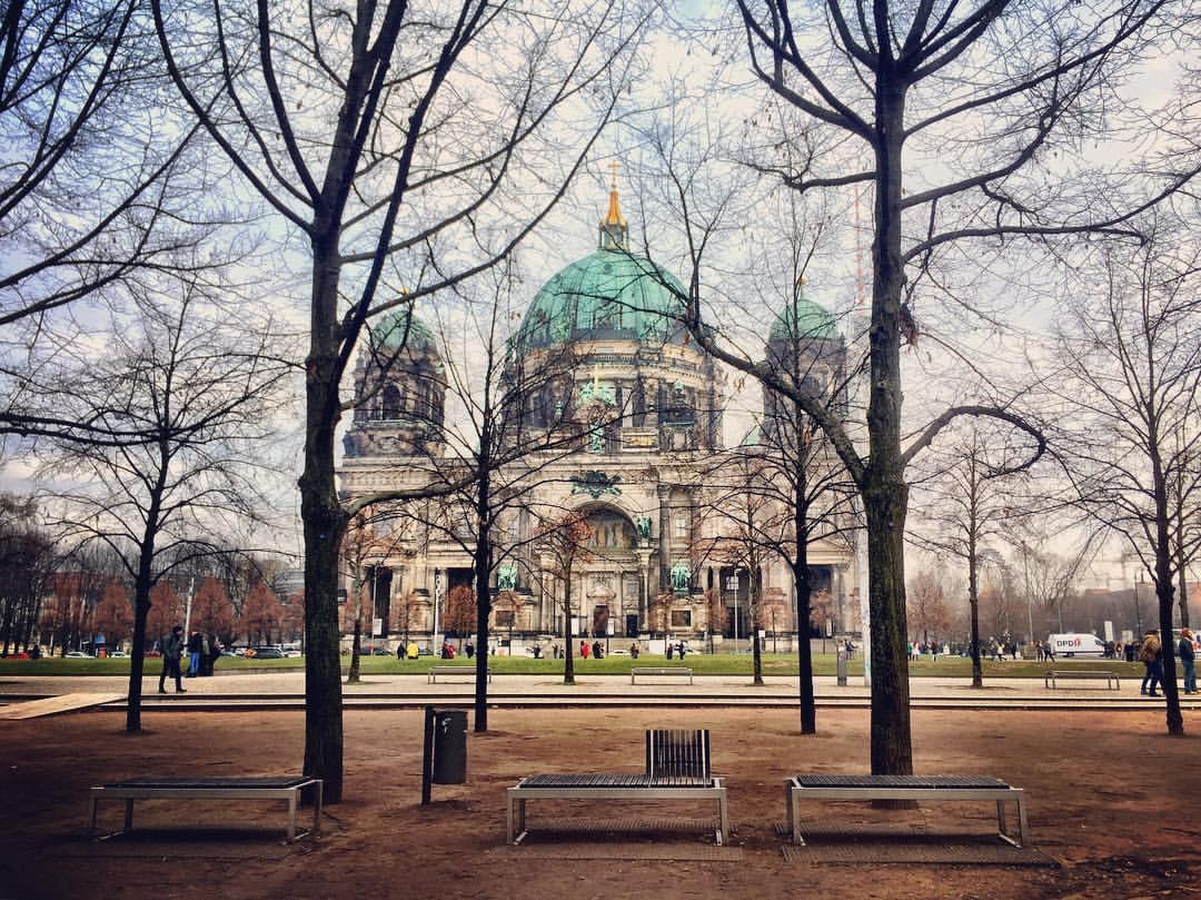 #paracegover A imagem mostra a Catedral de Berlin vista pelas árvores desfolhadas do Lustgarten. O clima é de paz e serenidade. — at Berliner Dom.