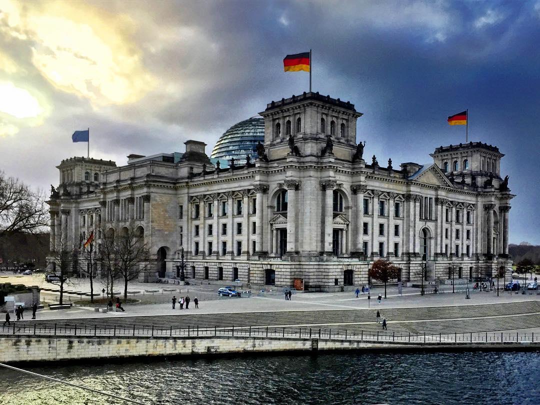 1. O parlamento alemão, com toda sua beleza! #paracegover A imagem mostra o prédio do Parlamento Alemão à beira do rio Spree. O céu está dramático. — at Berlin, Reichstag.