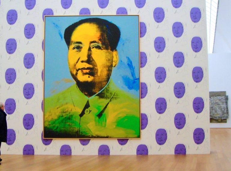 #paracegover A imagem mostra uma tela gigante de Andy Warhol exposta do Hamburger Bahnhof Museum, em Berlim, com um retrato de Mao Tse Tung no centro em uma parede branca estampada com grandes bolas da cor lilás.
