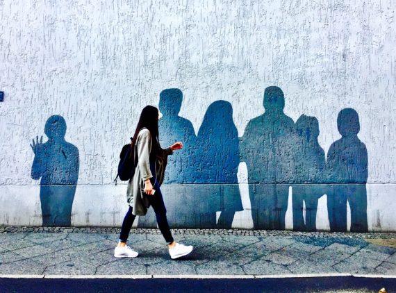 #paracegover A imagem mostra uma moça andando numa calçada. No muro atrás dela há uma série de silheutas de pessoas pintadas. Parecem sombras.