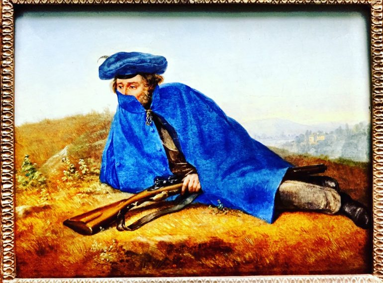 A imagem mostra a reprodução do quadro Auf Vorposten, de Georg Friedrich Kersting. Há um homem deitado sobre a relva. Ele está armado, usa uma capa azul e uma expressão infeliz.