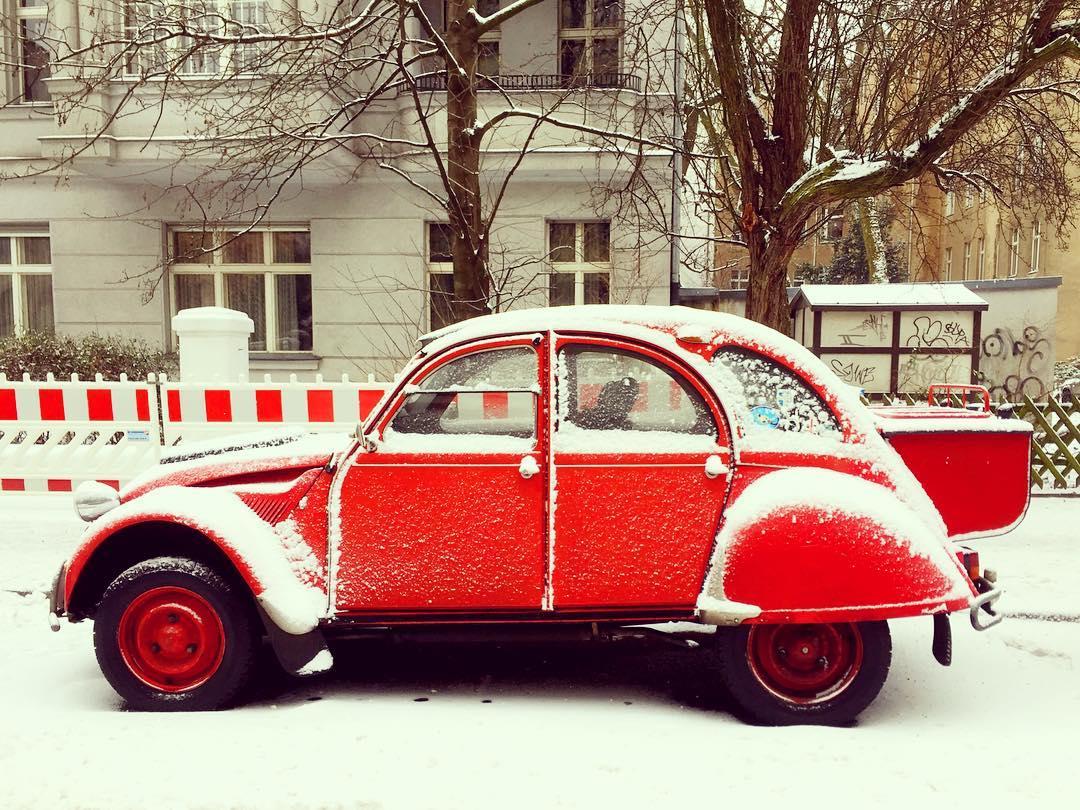 Descrição para deficientes visuais: a imagem mostra um Citröen antigo estacionado na rua. O vermelho intenso do carro da mesma cor dos detalhes da cerca de proteção atrás contrasta com a neve que cobre tudo. — at Volkspark Schöneberg