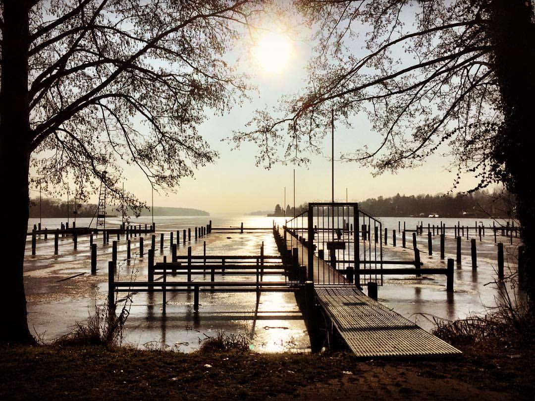 Descrição para deficientes visuais: a imagem mostra uma marina completamente vazia porque as águas do lago congelaram. Árvores emolduram a paisagem e o sol está baixo como se fossem cinco da tarde no Brasil. — at Am Pichelsee.