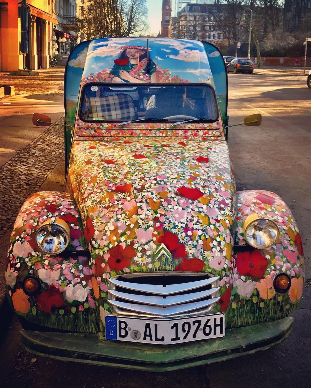 Descrição para deficientes visuais: a imagem mostra um carro antigo visto de frente (acho que é um Citröen) todo estampado com flores do campo. Na capota, o desenho de uma moça de cabelos pretos segurando uma rosa vermelha. O veículo é do restaurante francês Paulette, que fica no local onde ele está estacionado. Primavera ambulante � — at Knaackstraße.