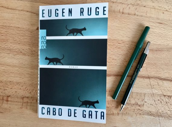 """A imagem mostra a caoa do livro """"Cabo de Gata"""". São três listras com um degradê que vai do verde ao preto sobre o fundo branco. Em cada uma, aparece a silhueta de um gato."""