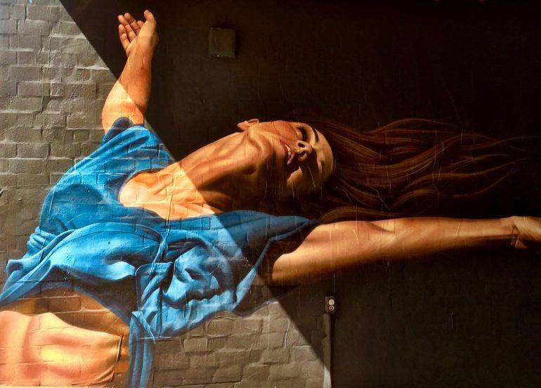 A imagem mostra um grafite hiperrealista de uma mulher se alongando com os braços abertos e uma blusa azul.
