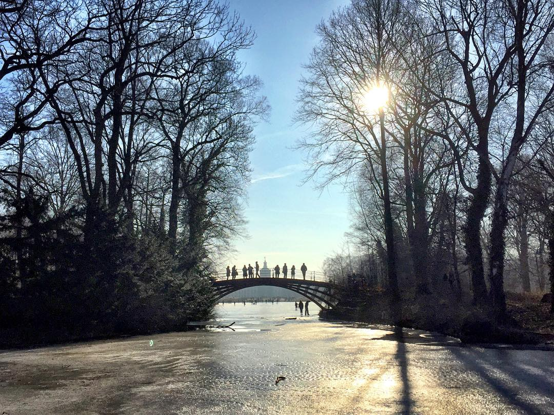 #paracegover Descrição para deficientes visuais: a imagem mostra uma ponte na parte de trás do Castelo de Charlottenburg. O lago embaixo dela está congelado. A vegetação tem apenas galhos. Muitas pessoas caminham sobre a ponte. O dia está lindo (mas a foto é do final de semana; hoje está bem nublado). — at Schlosspark Charlottenburg.