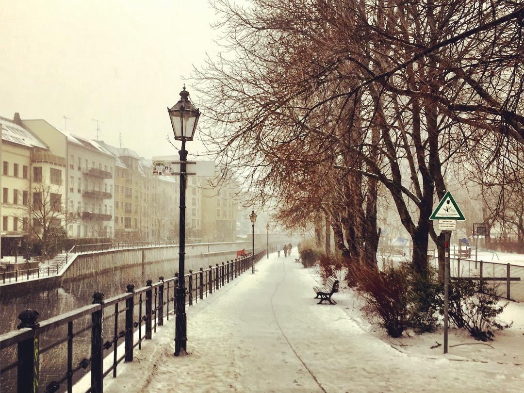 #paracegover Descrição para deficientes visuais: A imagem mostra uma das margens de um canal do rio Spree. Há uma luminária, um banco, árvores sem folhas e o chão coberto de neve. Faz frio. — at Derag Hotel und Living Grosser Kurfuerst Berlin.