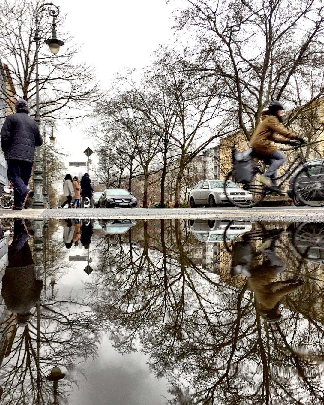 #paracegover Descrição para deficientes visuais: a imagem mostra uma rua onde passam pessoas, carros e ciclistas. Tudo, incluindo o poste de iluminação, o céu nublado e as árvores sem folhas, está refletido na poça d'água em primeiro plano. — at Gneisenaustraße.
