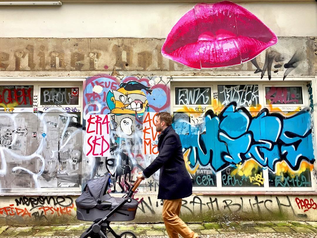 #paracegover Descrição para deficientes visuais: a imagem mostra um homem caminhando com um carrinho de bebê. Ao fundo, uma parede toda grafitada com um grande beijo pink em destaque. — at Gabriel-Max-Straße.