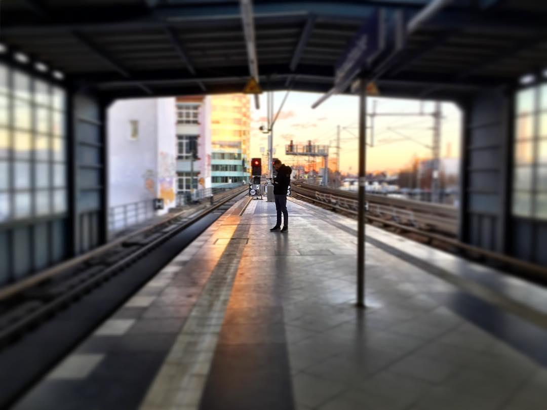 #paracegover Descrição para deficientes visuais: a imagem mostra uma estação de trem vista por dentro. Há uma pessoa na plataforma vazia, consultando seu celular. A luz do sol faz com que os prédios ao fundo fiquem dourados. — at Berlin Jannowitzbrücke station.