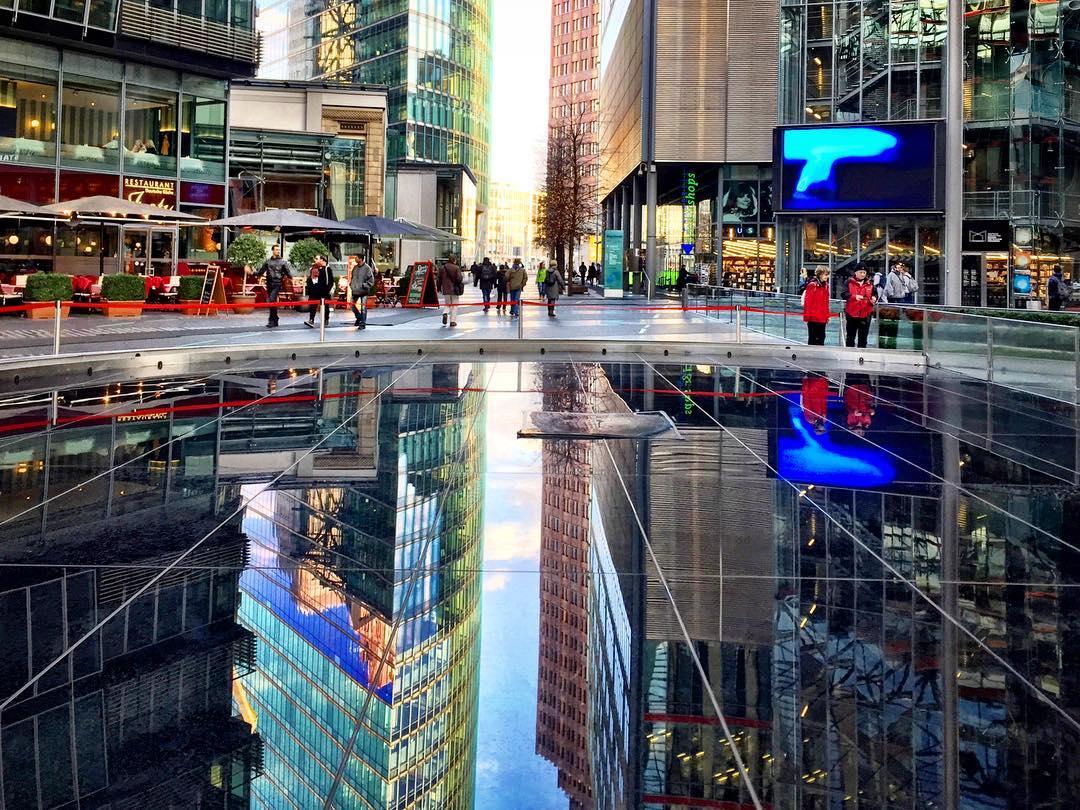 #paracegover Descrição para deficientes visuais: a imagem mostra a praça central do Sony Center, em Berlim. O piso de granito preto reflete a arquitetura desenhada em concreto, aço e muito vidro. — at Sony Center.