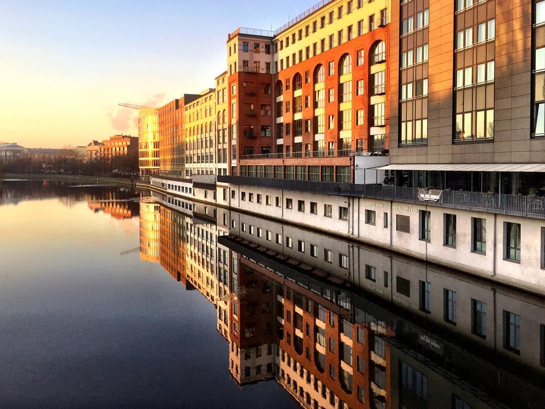 #paracegover Descrição para deficientes visuais: a imagem mostra o rio Spree visto de cima de uma ponte. Na margem esquerda, os prédios dourados pela luz do sol são refletidos na água. — at Gotzkowskybrücke.