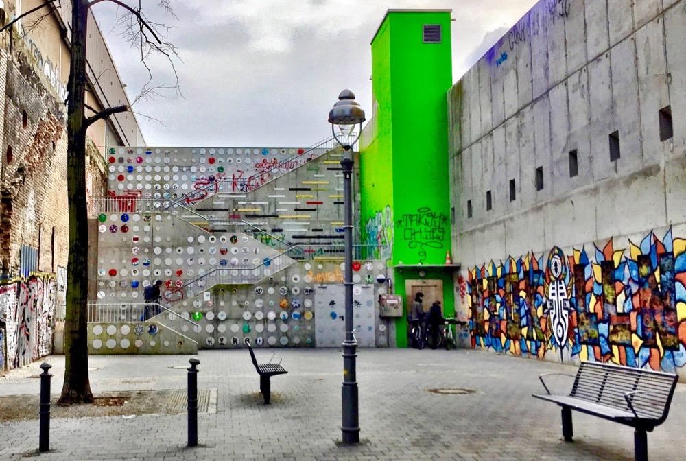 A imagem mostra um beco com uma escadaria de concreto no final, cheia de intervenções artísticas. Do lado direito há um elevador pintado de verde-limão.