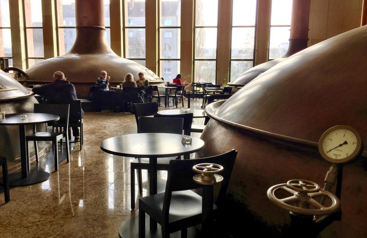A imagem mostra vários tonéis de cerveja em um salão. Há mesas em volta com algumas pessoas sentadas.