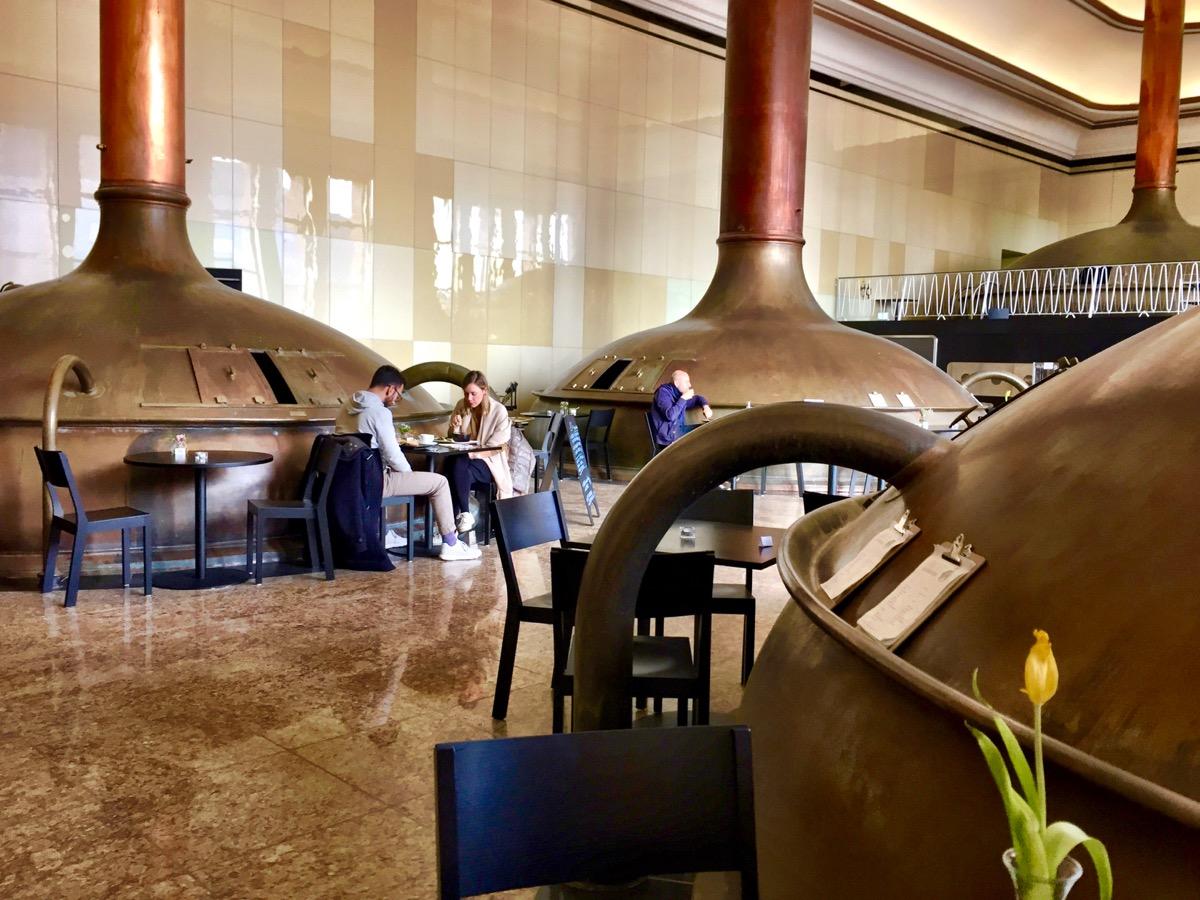 #paracegover Descrição para deficientes visuais: a imagem mostra pessoas sentadas em mesas ao lado dos tanques de cerveja. Em primeiro plano, pode-se ver os cardápios em pranchetas e uma tulipa amarela sobre uma mesa.