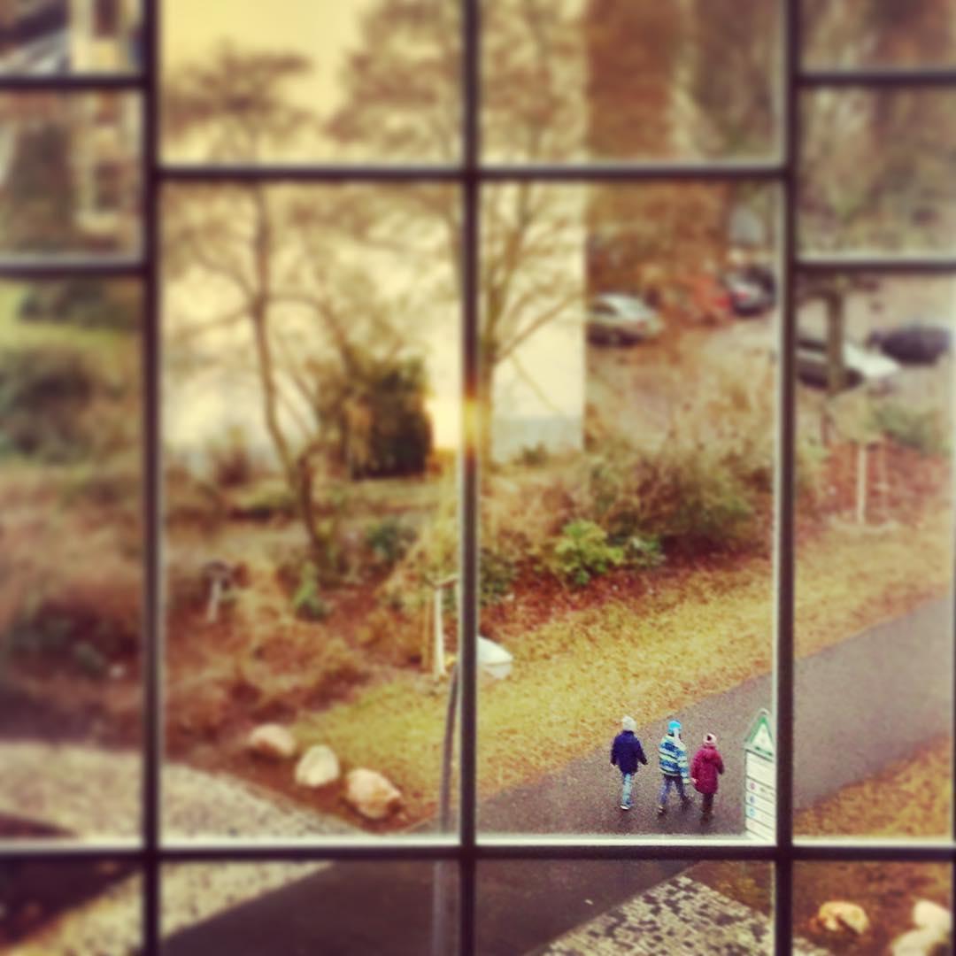 #paracegover Descrição para deficientes visuais: a imagem mostra três crianças caminhando em uma rua ao lado de uma praça. A cena é vista através das esquadrias de uma janela. — in Schöneberg, Berlin, Germany.