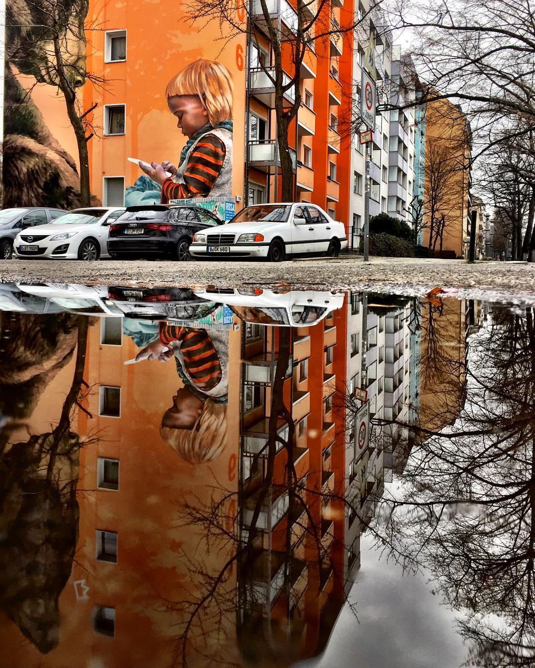 #paracegover Descrição para deficientes visuais: a imagem mostra um grafite na esquina de um prédio residencial pintado em tons de laranja. A obra representa uma criança lendo algo para um enorme urso polar castanho. Os dois parecem muito entretidos. A cena está toda refletida na poça d'água à frente, com a participação indesejada de carros estacionados no local. As árvores ainda estão todas sem folhas. — at Park am Gleisdreieck.
