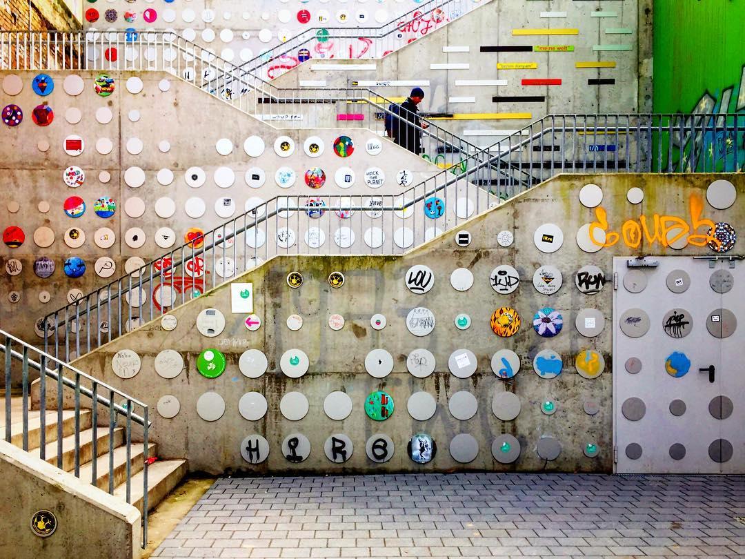 #paracegover Descrição para deficientes visuais: a imagem mostra uma escada externa com vários níveis, vista de lado. As paredes estão cobertas com uma instalação de arte composta de discos de metal onde vários artistas fizeram intervenções. Há um homem de preto descendo a escada enquanto consulta o celular. — at KINDL - Zentrum für zeitgenössische Kunst.