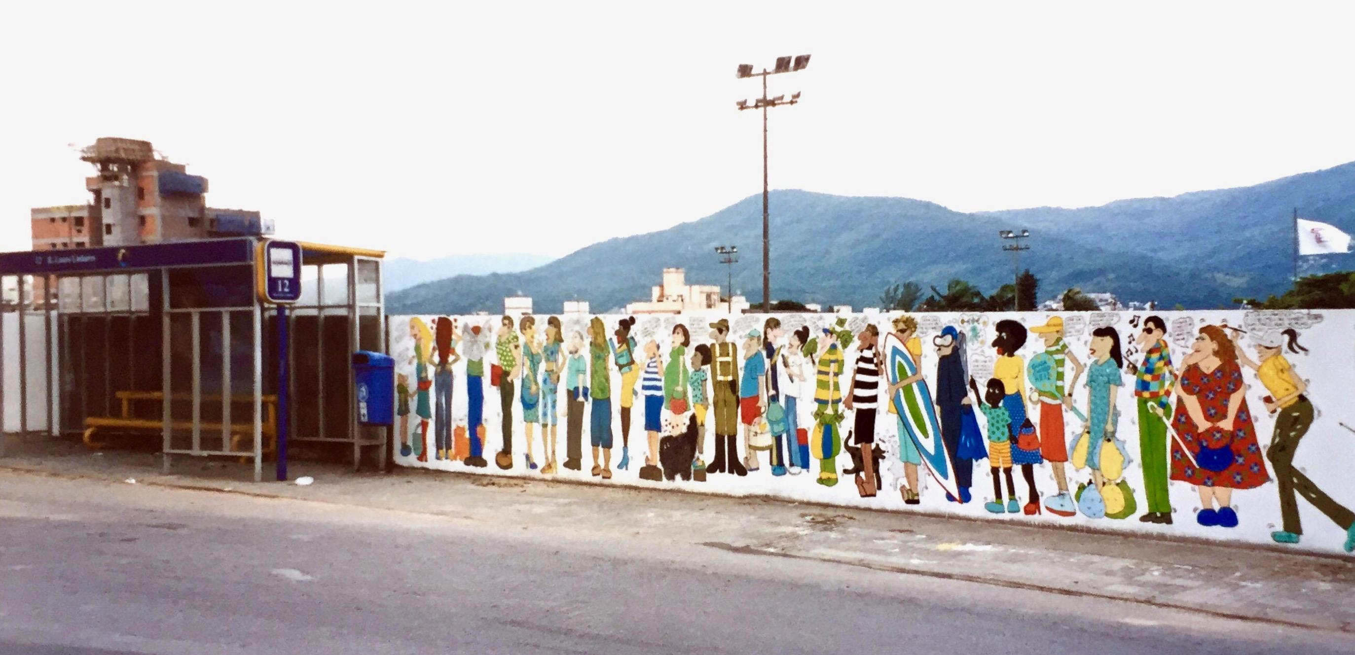 #paracegover A imagem mostra um ponto de ônibus coberto.No muro ao redor dele, personagens desenhados conversando entre si.