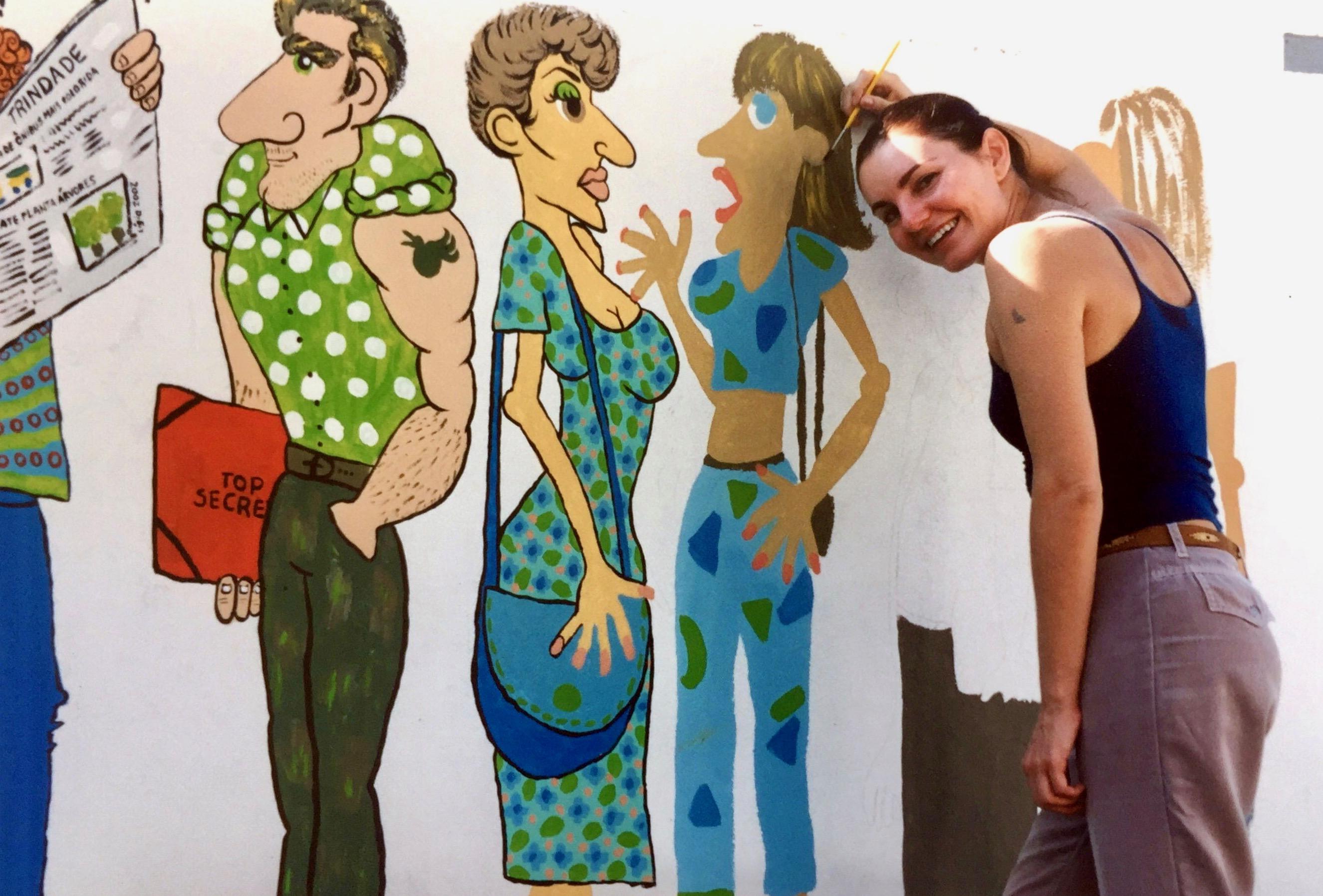#paracegover A imagem mostra uma mulher sorrindo ao lado de um muro com desenhos inacabados.