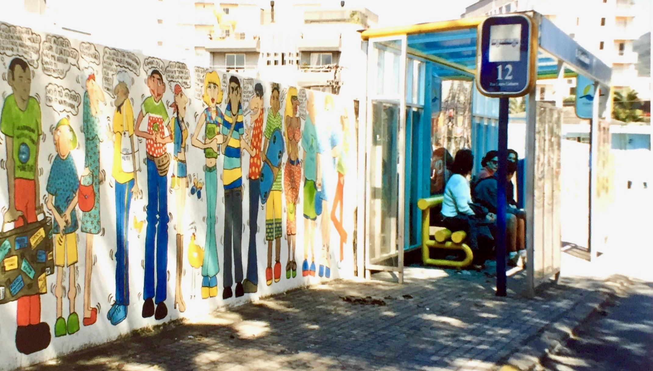 #paracegover A imagem mostra pessoas sentadas no ponto de ônibus ao lado do muro desenhado.