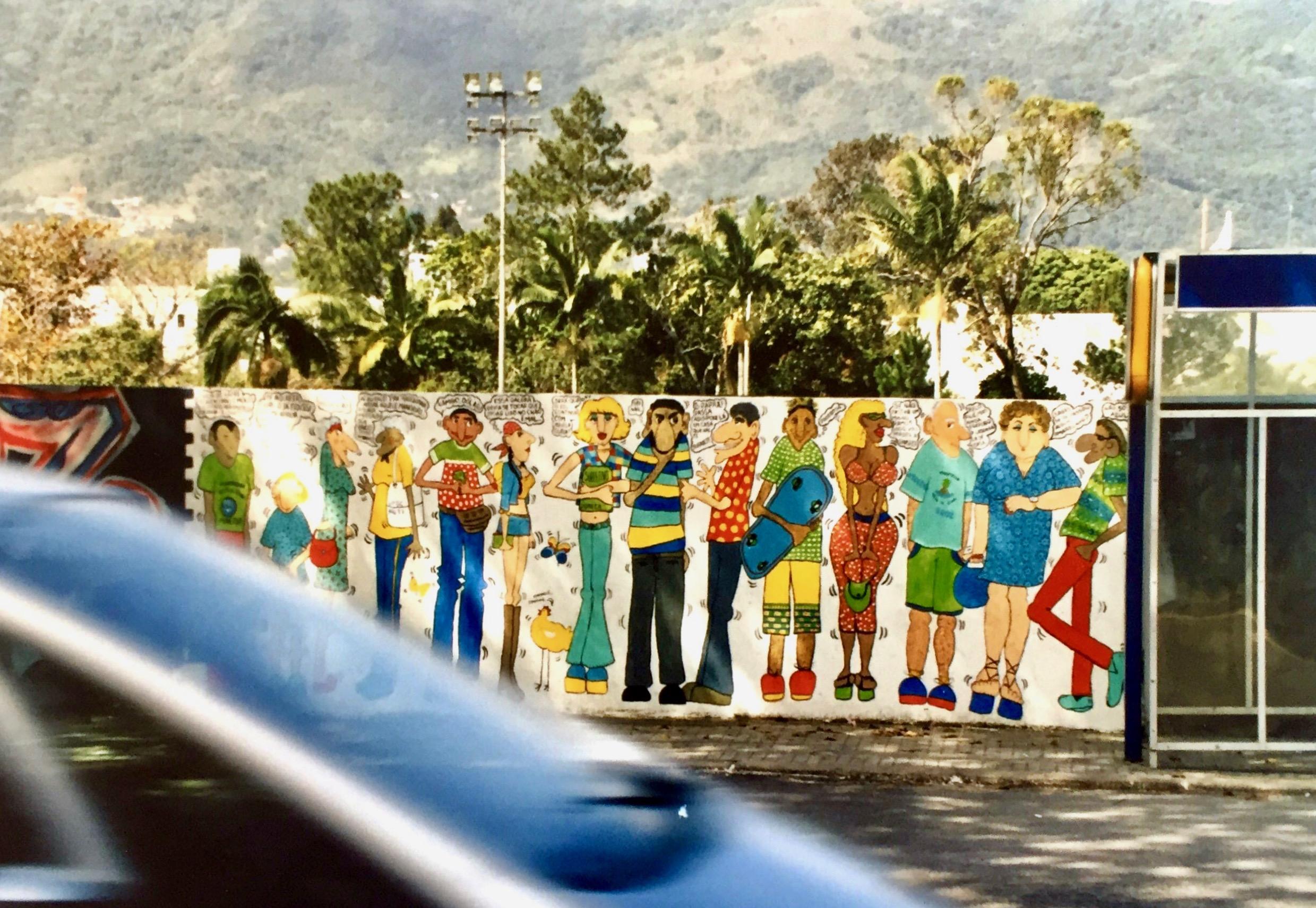 #paracegover A imagem mostra um muro desenhado com pessoas em volta de um ponto de ônibus. A foto foi tirada do outro lado da rua e um carro passou bem na hora.