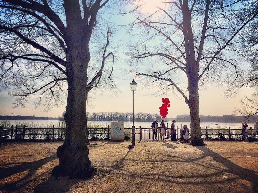 #paracegover Descrição para deficientes visuais: a imagem mostra um grupo de pessoas às margens do lago Tegel. A vegetação ainda está sem folhas. Uma das pessoas carrega um monte de balões vermelhos. Na verdade, acredito que estavam fotografando para uma campanha publicitária ou algo do gênero, a julgar pelo figurino do casal e o tamanho das lentes da fotógrafa 😊 — at Greenwichpromenade.