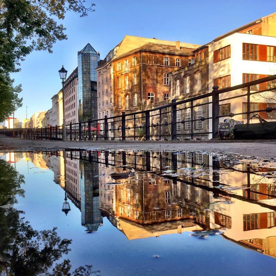 #paracegover Descrição para deficientes visuais: a imagem mostra um conjunto de prédios banhados pela luz dourada do sol, às margens de um dos canais do rio Spree. A cena é refletida numa poça d'água. — at Derag Hotel und Living Grosser Kurfuerst Berlin.