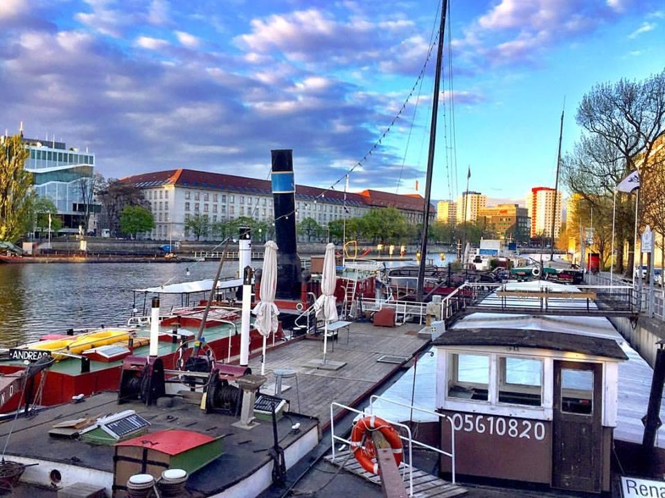 #paracegover Descrição para deficientes visuais: a imagem mostra barcos do porto histórico de Berlin sob um céu que varia do lilás ao turquesa. — at Historischer Hafen Berlin.
