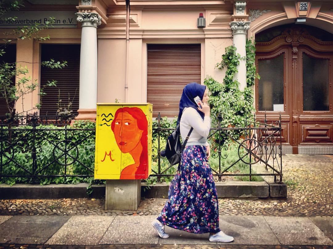 #paracegover Descrição para deficientes visuais: a imagem mostra uma mulher muçulmana caminhando por uma calçada falando no celular (lenço azul marinho e saia longa estamapada no mesmo tom; blusa e tênis claros). Atrás dela, uma pintura na caixa de eletricidade do prédio, mostra a cabeça desenhada de uma mulher em um laranja sob fundo amarelo olhando atentamente para a passante. Não apenas as cores, mas as atitudes (atenta x distraída) também são complementares. — at Crellestr.7.