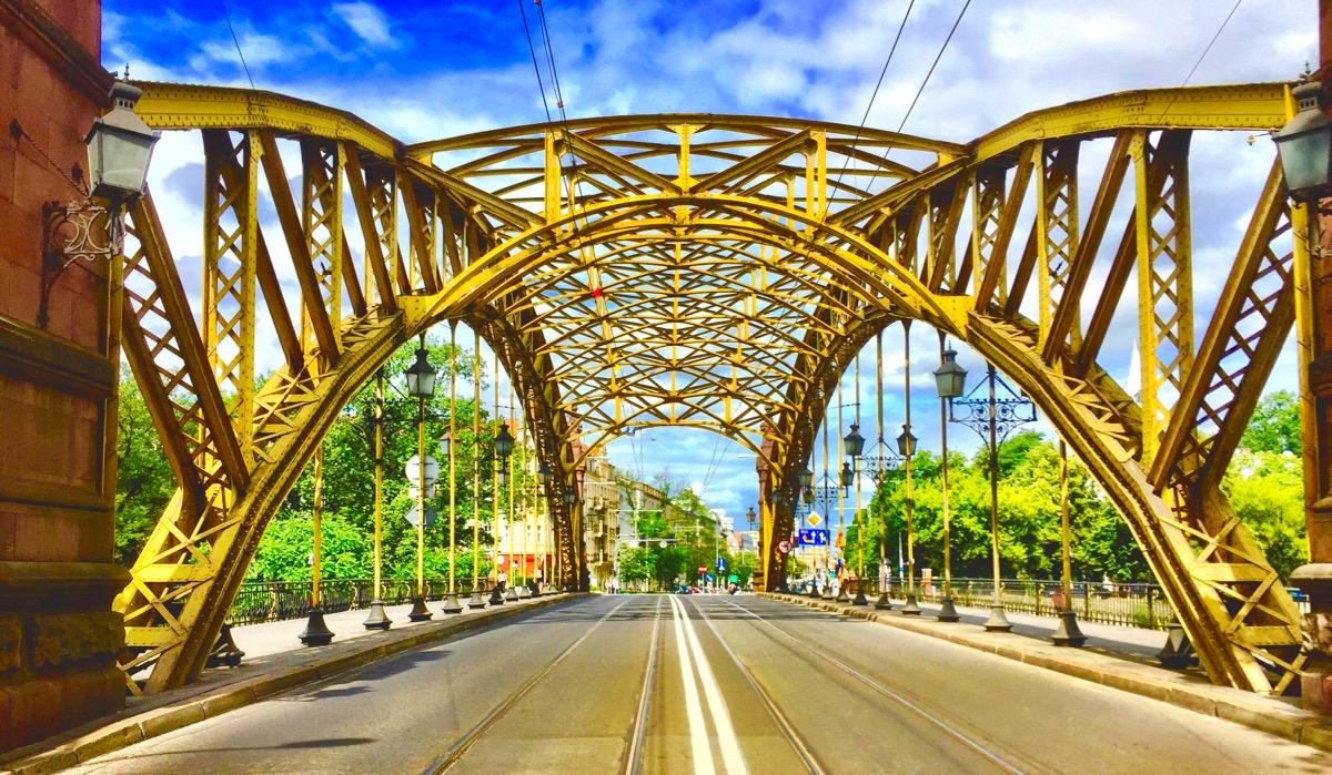 A imagem mostra uma ponte vista do vão central. Ela é de ferro e pintada de amarelo.