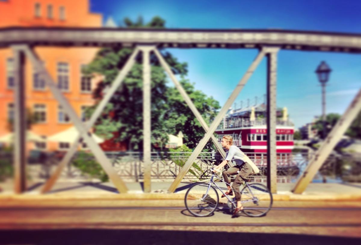 A imagem mostra uma mulher passando de bicicleta por uma ponte de ferro.