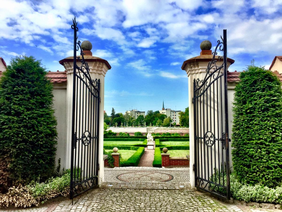 A imagem mostra um portão de entrada de um belíssimo e bem cuidado jardim.