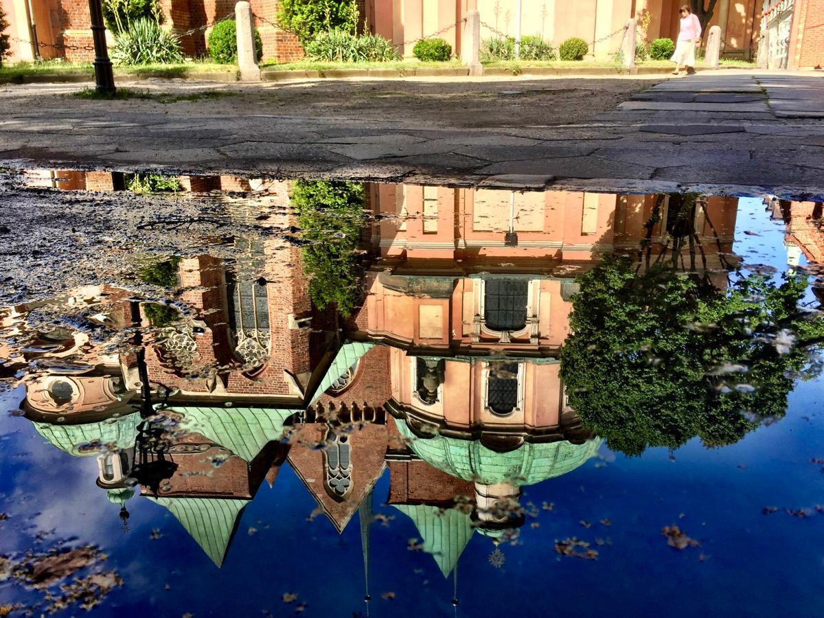 A imagem mostra o reflexo de um prédio histórico numa poça d'água.