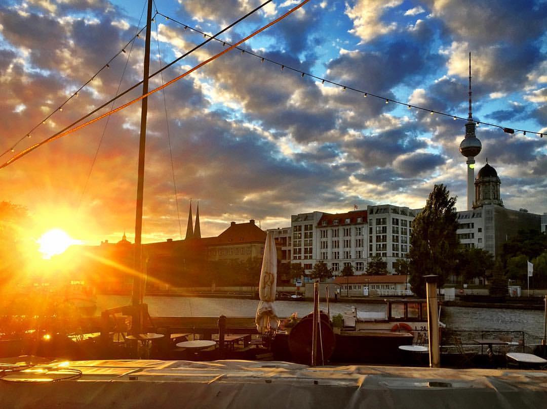 #paracegover Descrição para deficientes visuais: a imagem mostra o porto histórico coberto pela luz dourada do sol que se põe, quase 9 horas da noite. O céu ainda tem algumas nuvens, mas está limpando. — at Historischer Hafen Berlin.