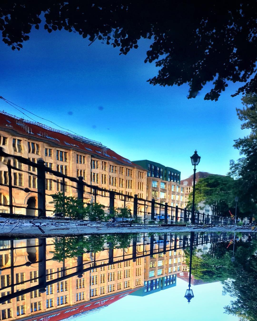 #paracegover Descrição para deficientes visuais: a imagem mostra o casario às margens de um canal do rio Spree refletido numa poça d'água. O dia promete. — at Historischer Hafen Berlin.